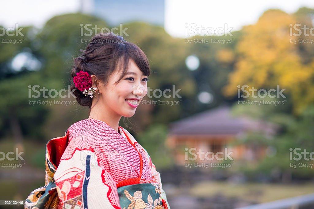 Young furisode girl smiling in garden stock photo