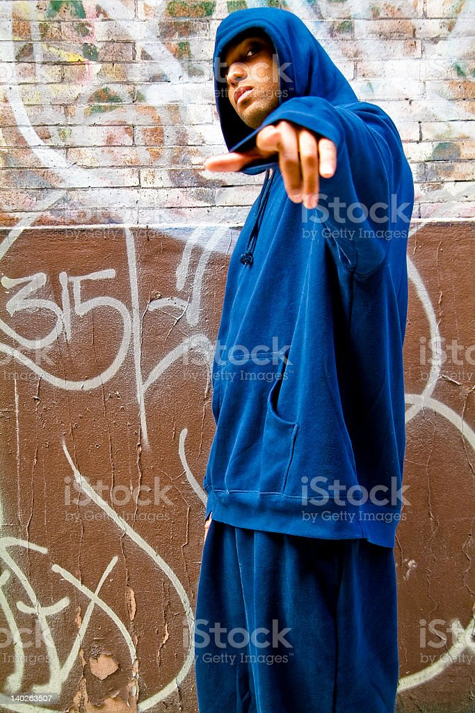 Young Gangsta Male in Hoodie against Graffiti street wall stock photo