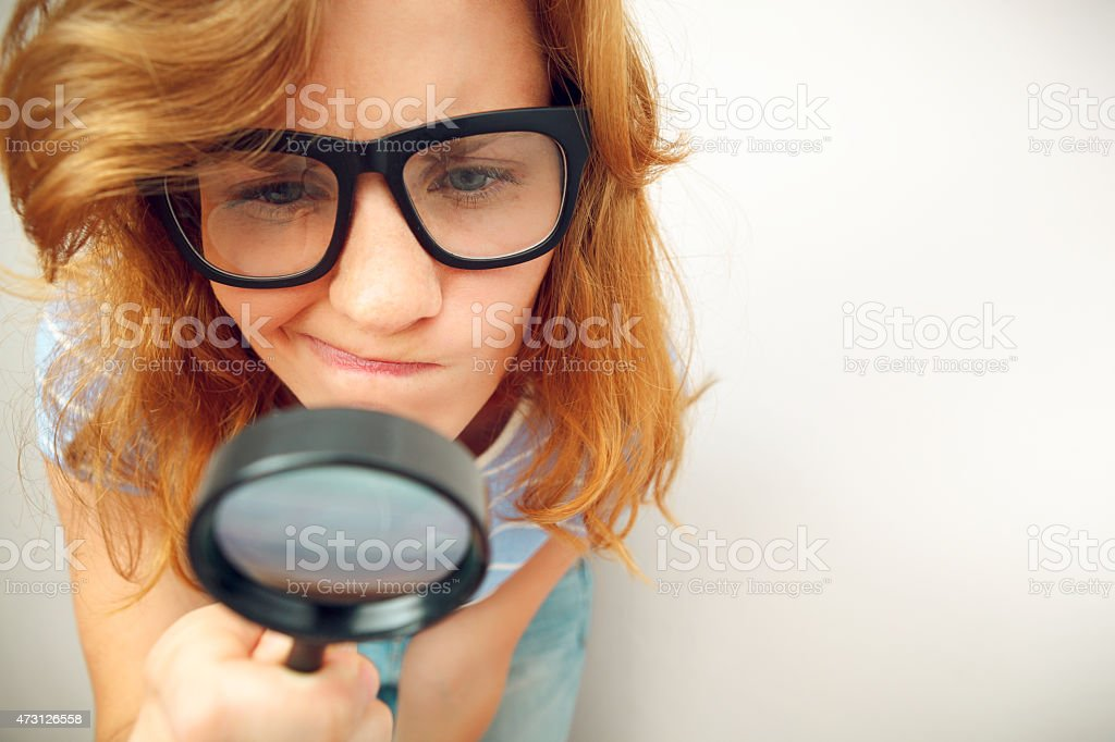 Young geek looking through magnifying glass. stock photo
