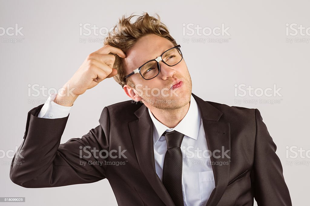 Young geeky businessman scratching his head stock photo