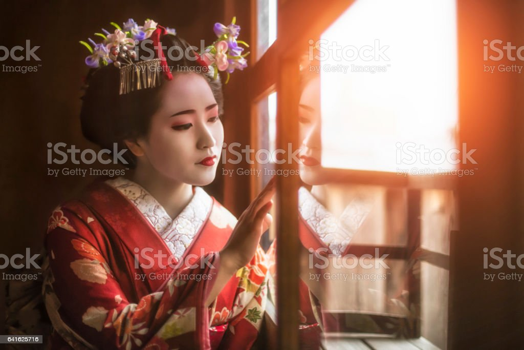 Young geisha girl looking through window stock photo