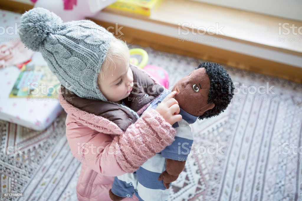 A young German playing with her black doll stock photo
