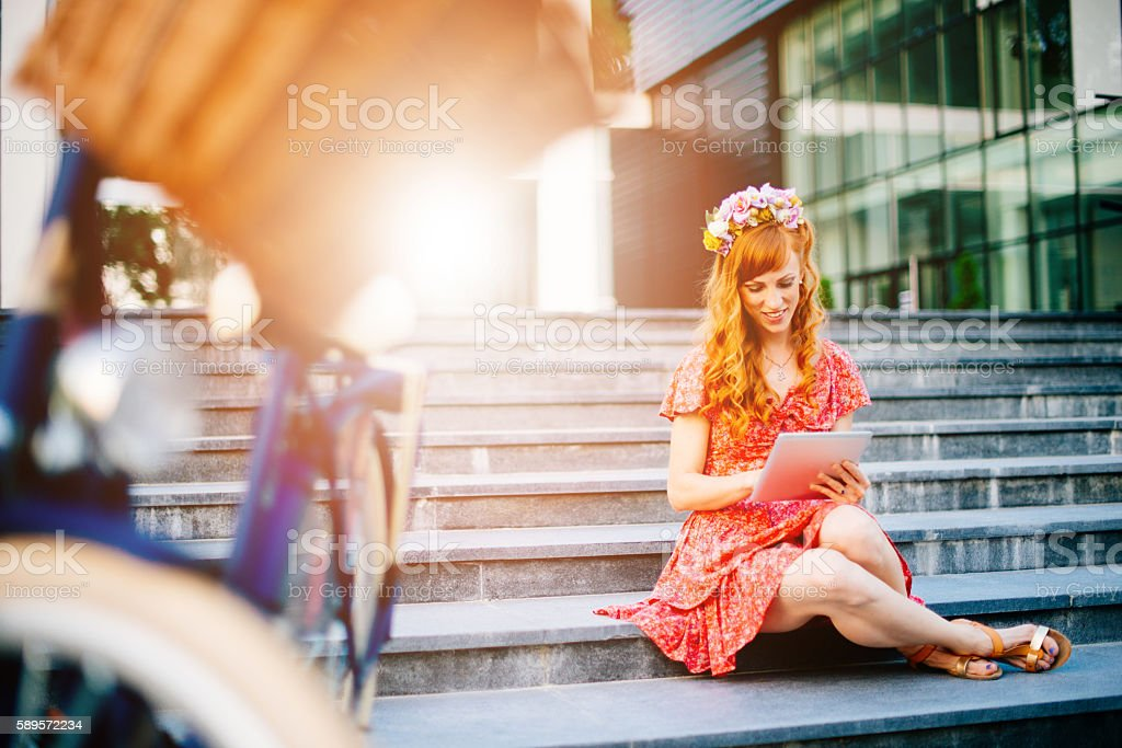 Young ginger woman in summer using laptop stock photo