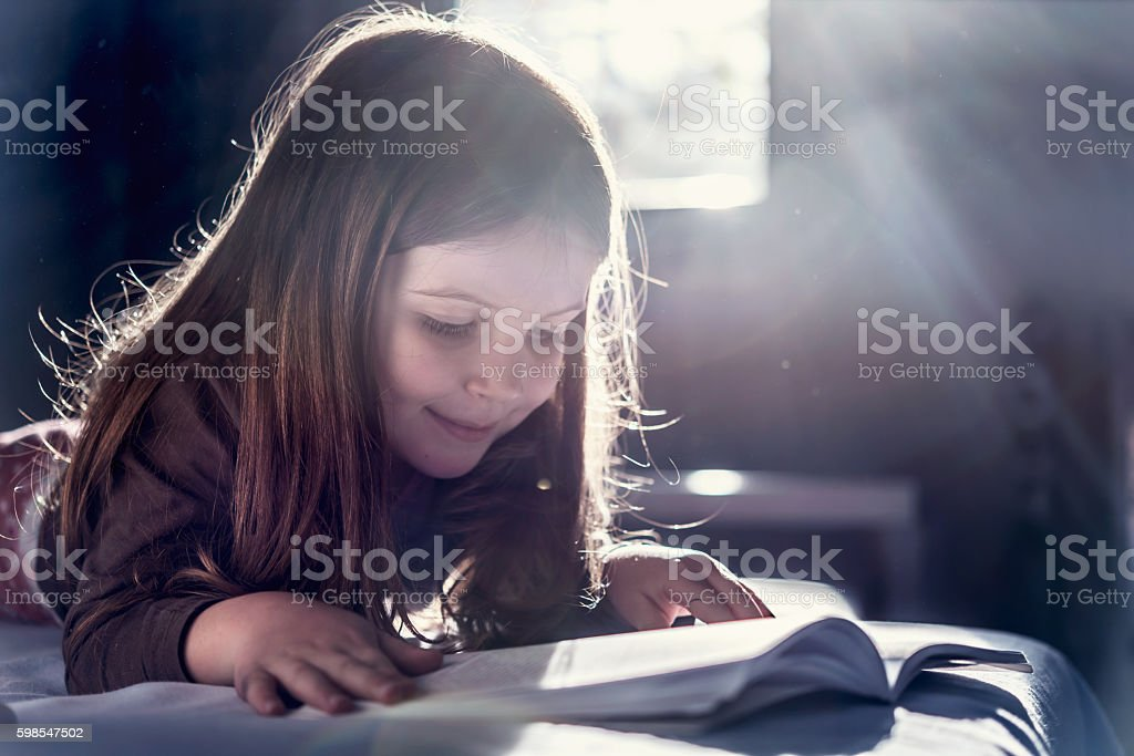 Young Girl Addicted to Reading stock photo