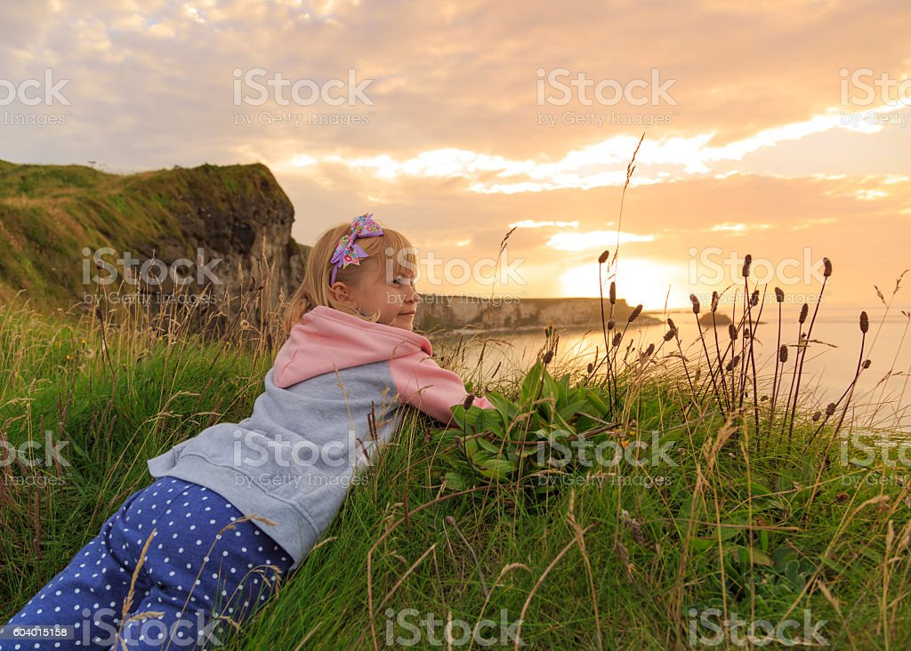 Young girl admires a beautiful landscape during sunset. stock photo