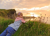 Young girl admires a beautiful landscape during sunset.