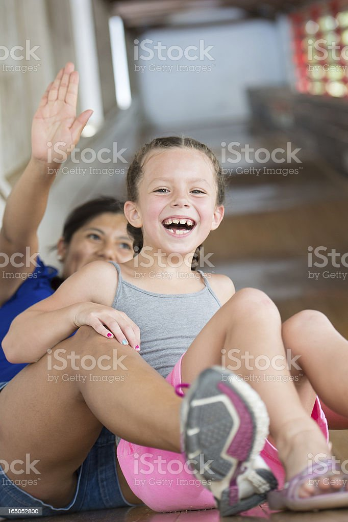 Young Girl and Au Pair Laughing on Large Wooden Slide royalty-free stock photo