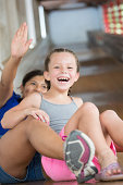 Young Girl and Au Pair Laughing on Large Wooden Slide