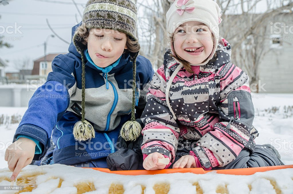 Young girl and boy eating maple syrup taffy outside stock photo