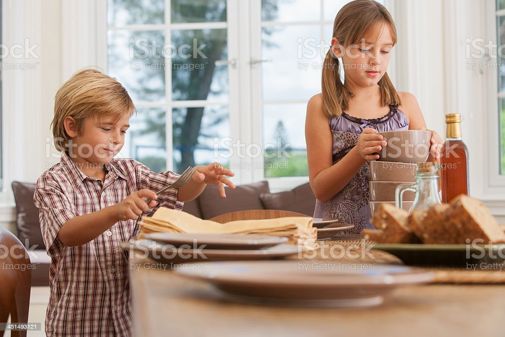 Young girl and boy in dining room setting table stock photo