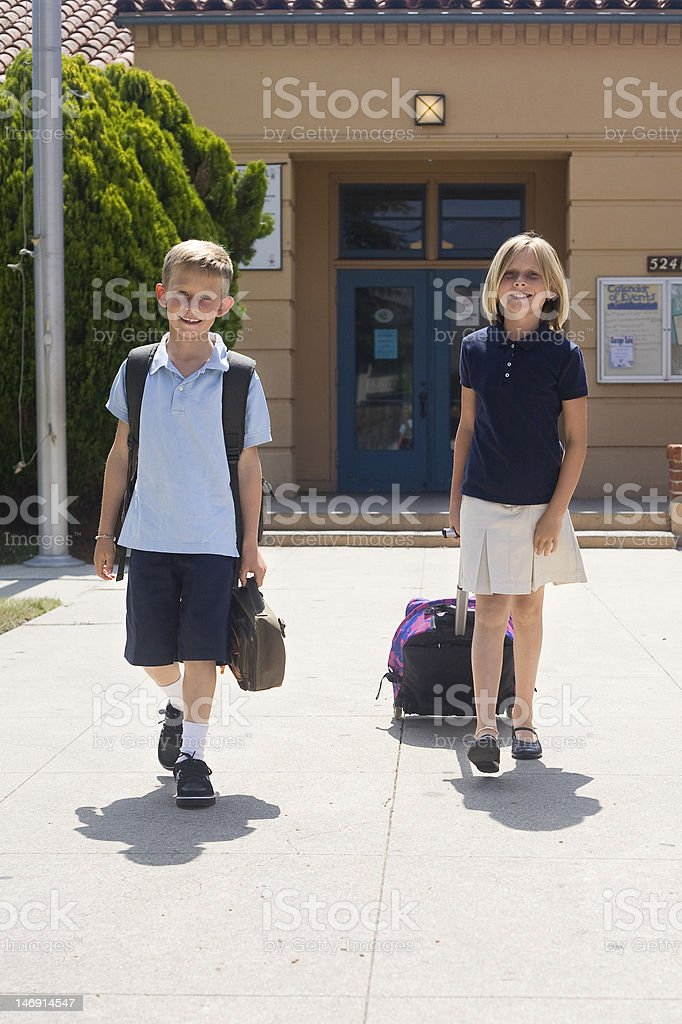 Young Girl and boy leave school stock photo