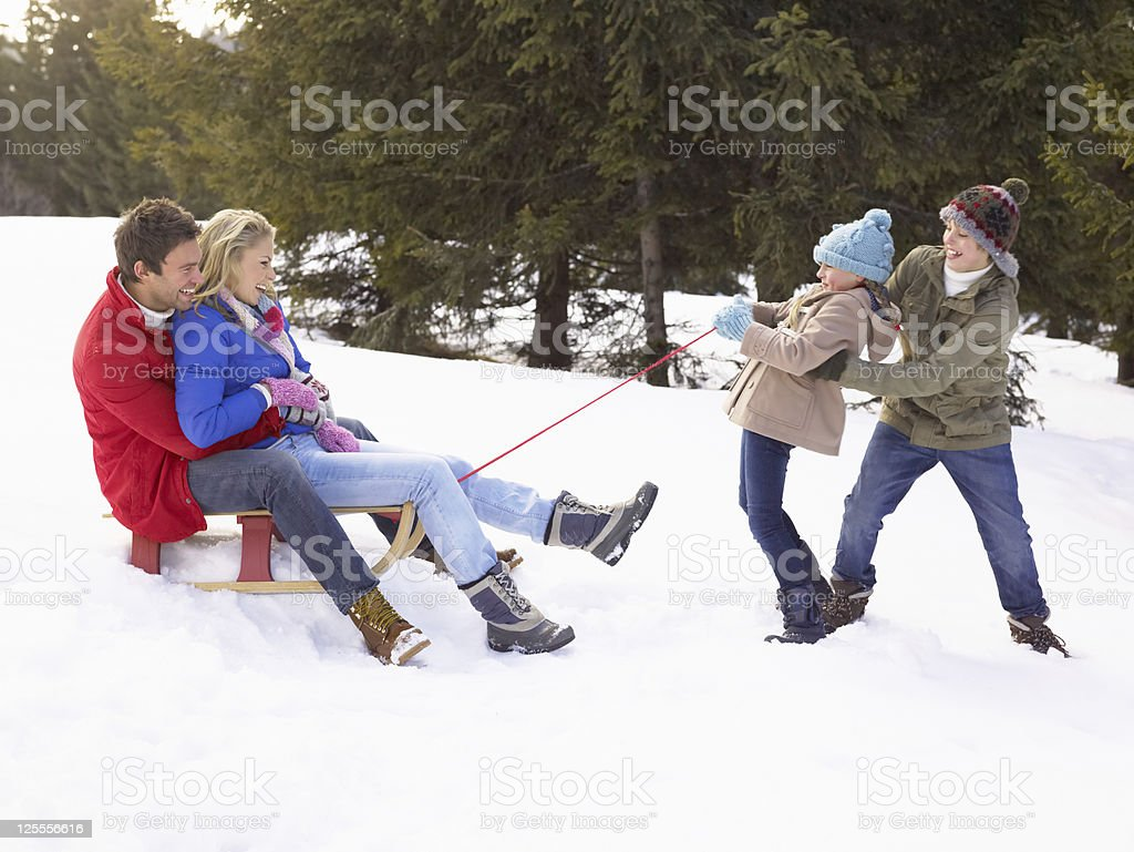 Young Girl And Boy Pulling Parents Through Snow On Sled stock photo