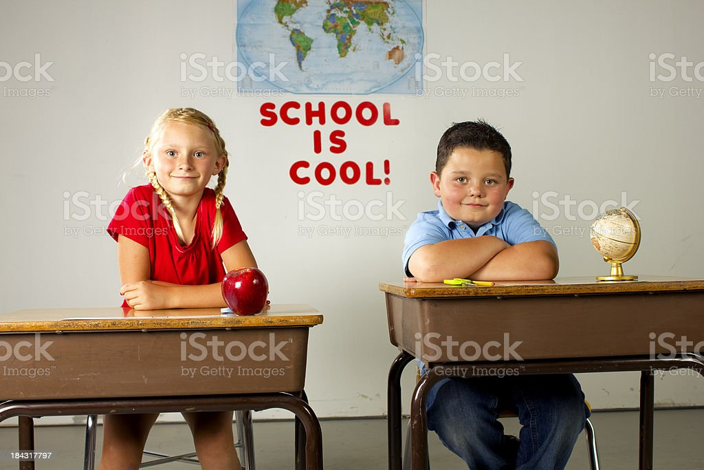 young girl and boy sitting in class stock photo