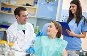 Young girl and dentist with assistant are satisfied after repair
