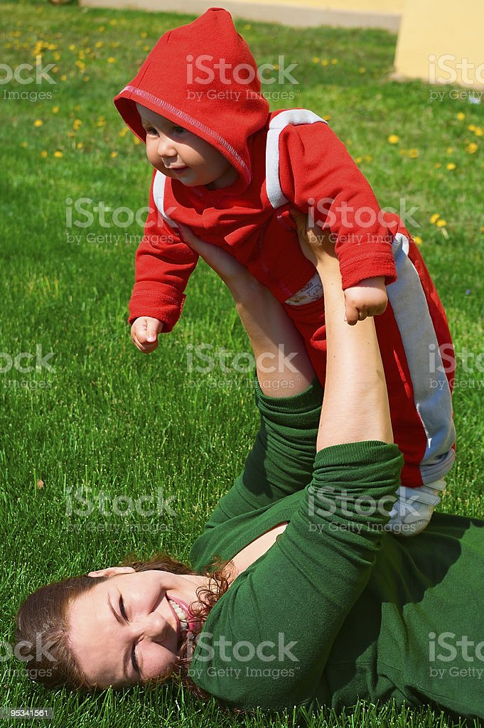 Young girl and her child lie on the green grass stock photo