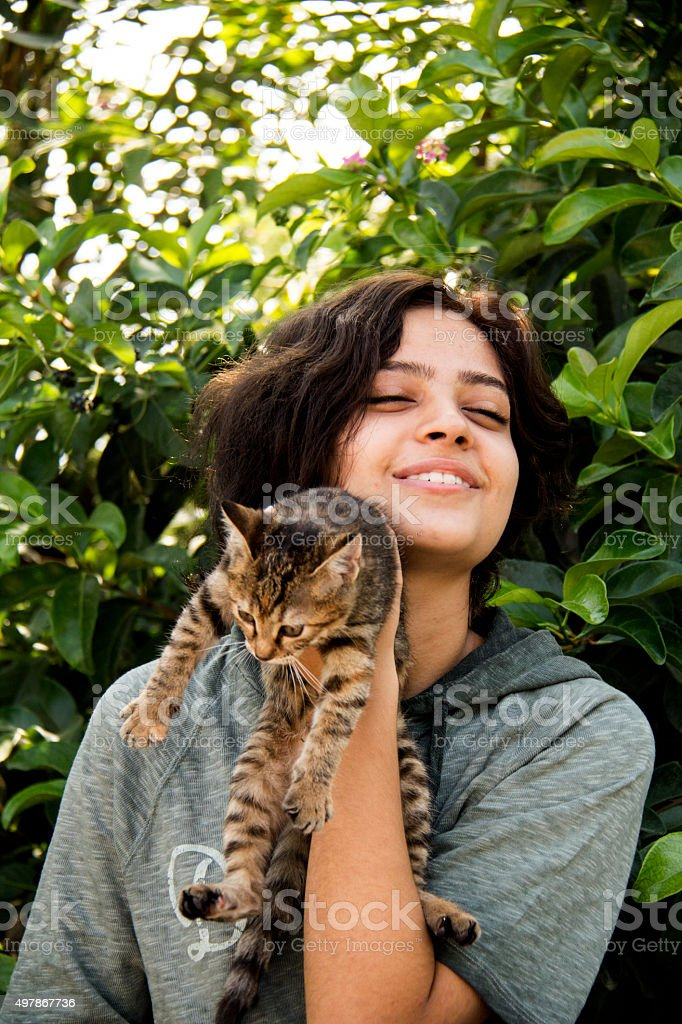 Young girl and hungry stray cat. stock photo