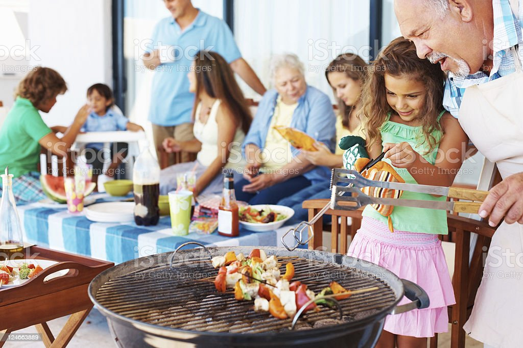 Young girl and older man grilling at barbecue royalty-free stock photo