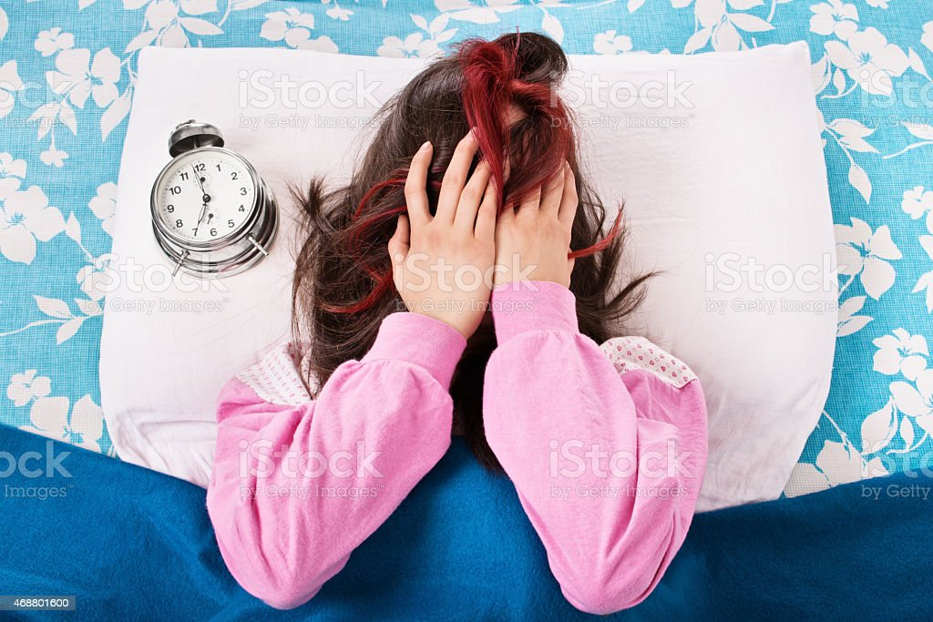 Young girl annoyed by the alarm clock stock photo