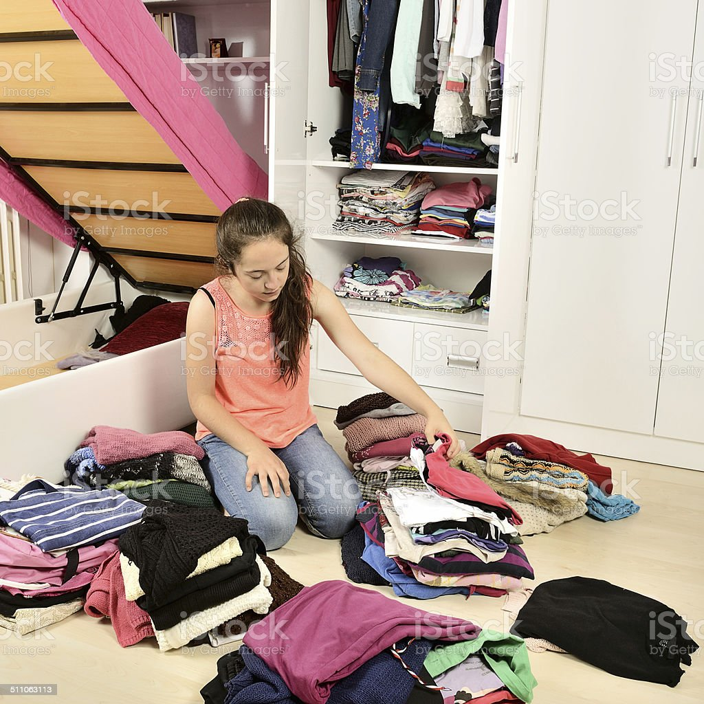 Young girl arranging her clothes stock photo