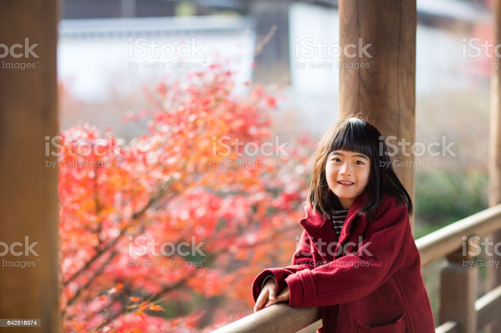 Young girl at a temple enjoying autumn leaves stock photo