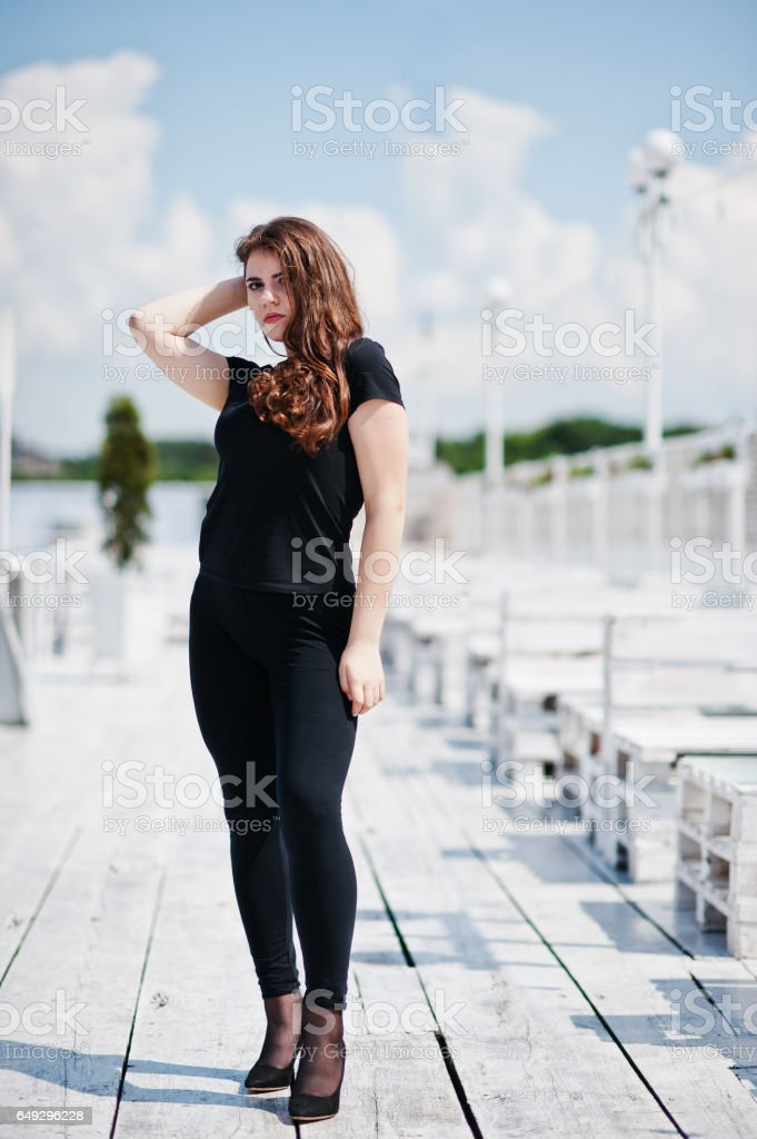 Young girl at black clothes posed on the pier stock photo