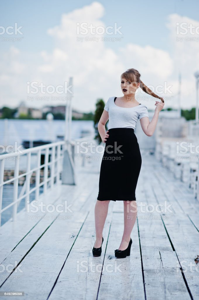 Young girl at black dress and black lips posed on the pier stock photo