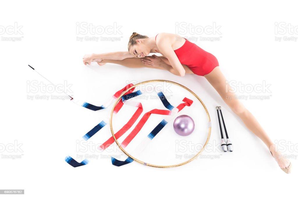 young girl athlete stretching near rhythmic gymnastics apparatus stock photo