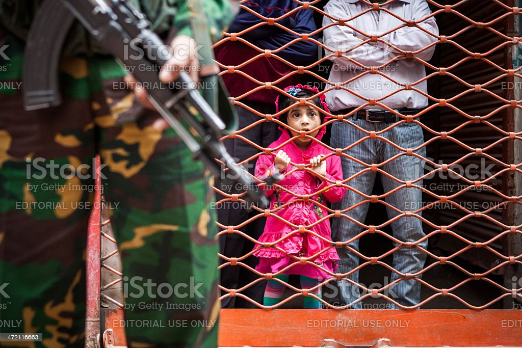 Young girl behind military stock photo