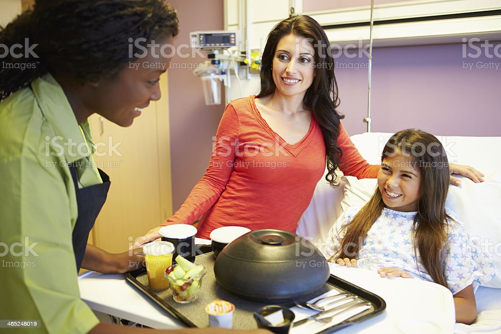 Young Girl Being Served Lunch In Hospital Bed stock photo