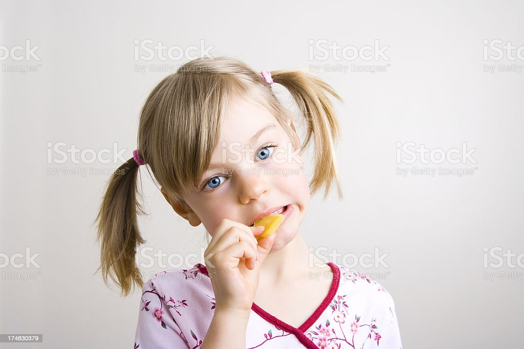 Young girl biting into a slice of cheese royalty-free stock photo