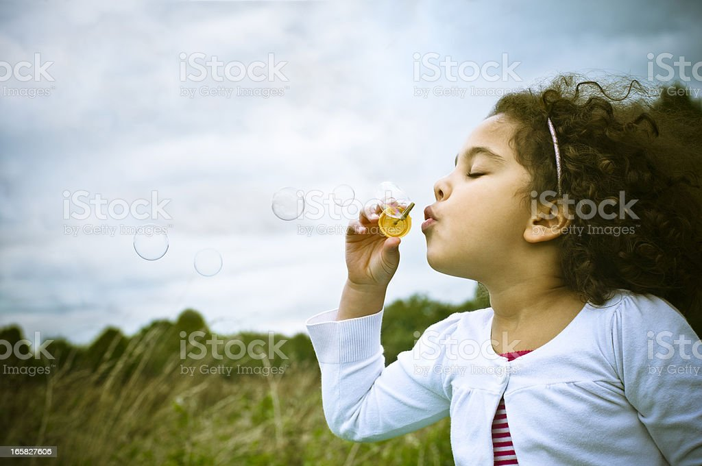 Young girl blowing bubbles with a wand stock photo