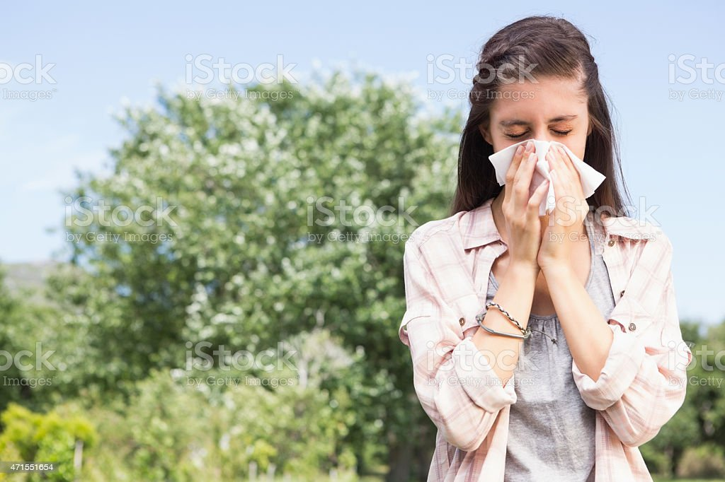 A young girl blowing her nose outdoors stock photo