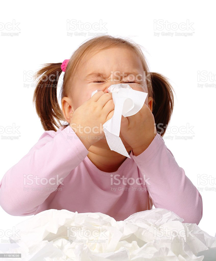 Young girl blowing her nose with pile of used tissues royalty-free stock photo