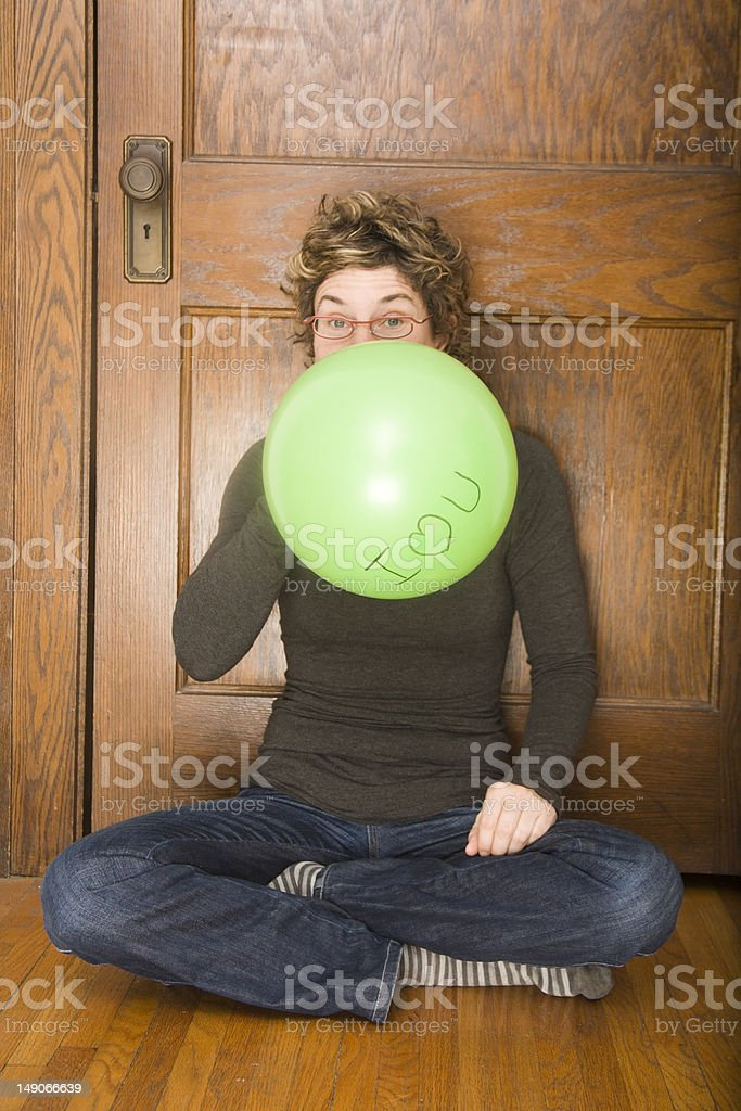 Young girl blowing up I Heart You balloon. royalty-free stock photo