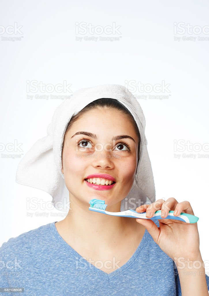 Young girl brushing teeth and looking up stock photo
