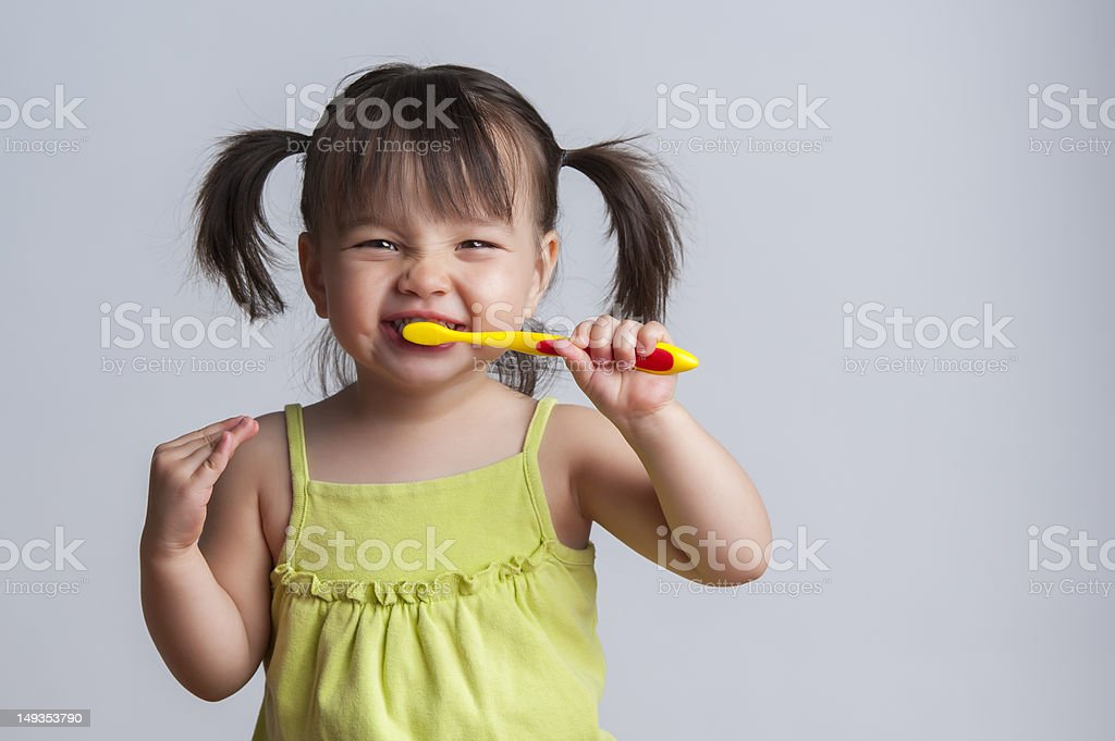Young girl brushing teeth with yellow toothbrush stock photo