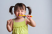 Young girl brushing teeth with yellow toothbrush