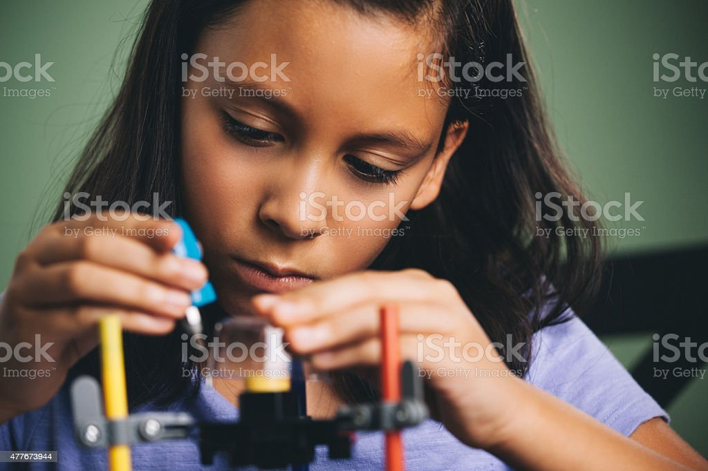 young girl building a robot stock photo