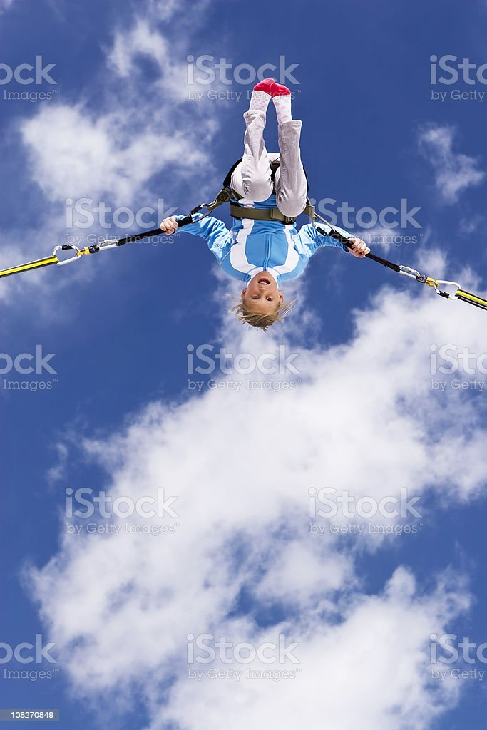 young girl bungee jumping up to clouds in blue sky stock photo