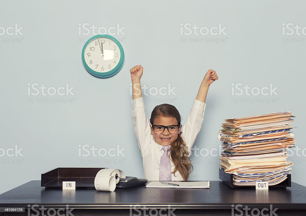 Young Girl Businesswoman Raises Arms at Office Desk stock photo