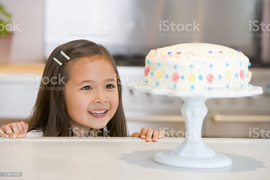 Young girl by kitchen counter looking at cake smiling stock photo