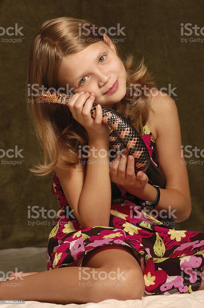 Young girl cares for a colorful snake. stock photo