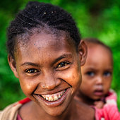 Young girl carrying her little brother, Ethiopia, East Africa
