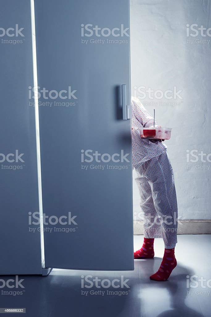 Young Girl Caught Getting Late Night Snack From The Fridge stock photo
