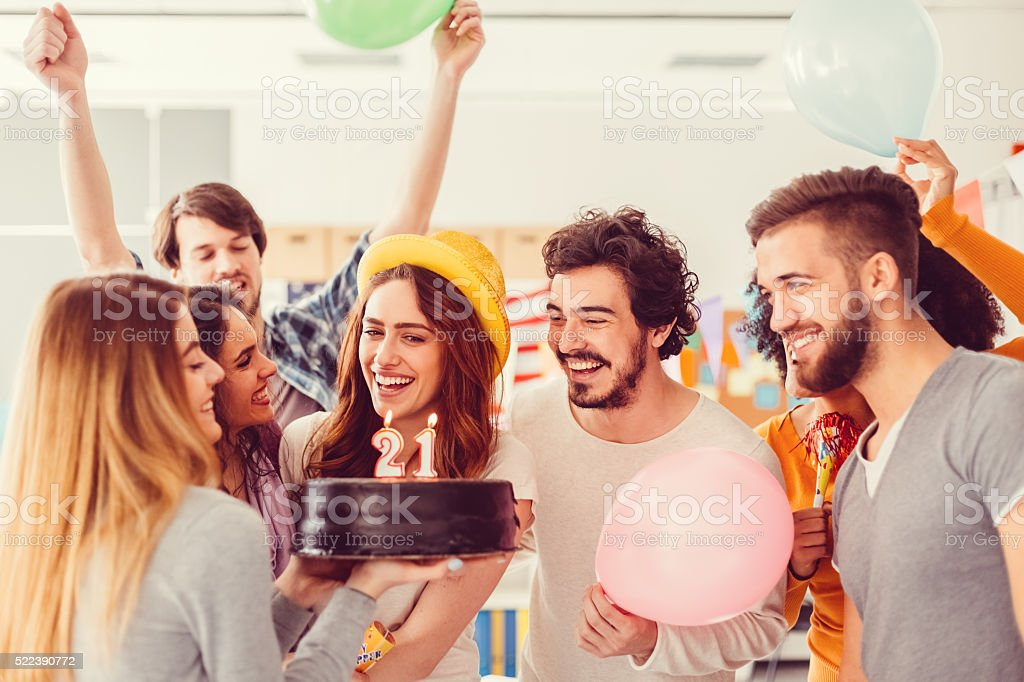 Young girl celebrating her 21st birthday with friends stock photo