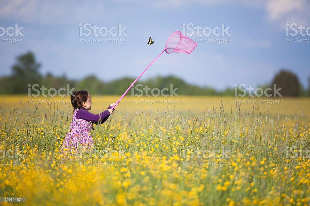 Young Girl Chasing Butterfly stock photo