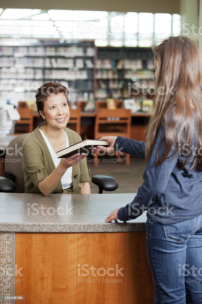 Young girl checking out a book from the library stock photo