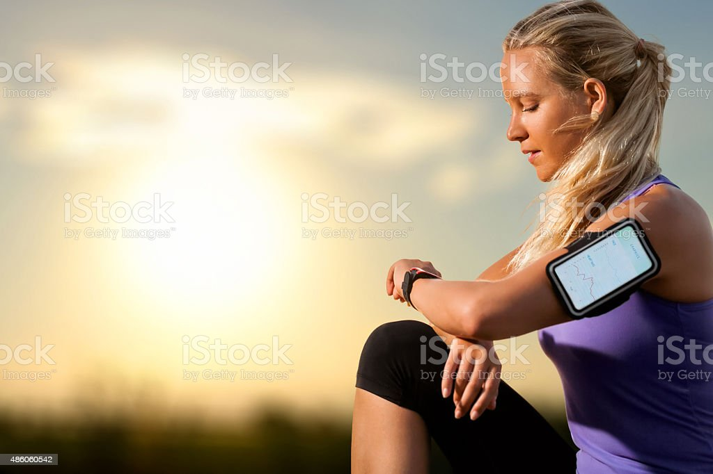 Young girl checking workout on smart watch at sunset. stock photo