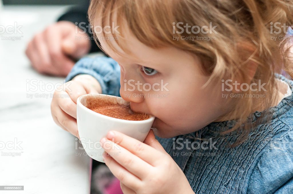 Young girl, child drinking from a cup stock photo