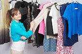 Young girl chooses clothes in the wardrobe